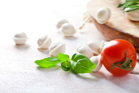 Tortellini and vegetables on white wooden background photo