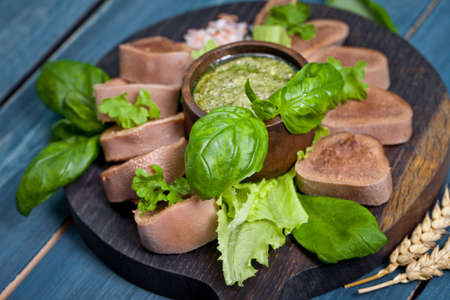 Boiled beef tongue on dark wooden table with pesto and salad Stok Fotoğraf