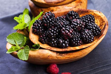 Ripe blackberries with leaves of mint in a bowl on a wooden board on dark background