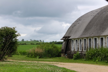 Old grey barn in cloudy landscape Stock Photo