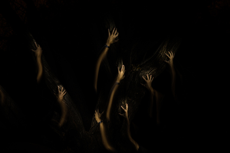 strange hands climbing up a tree in the dark Stock Photo