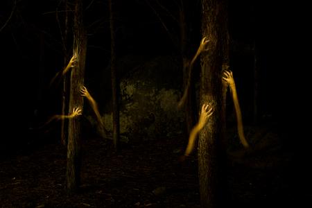 strange hands climbing up a tree in the dark Foto de archivo