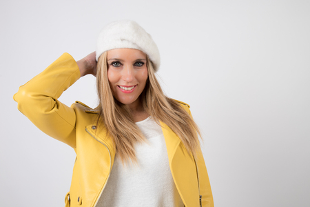 Woman with blonde hair and blue eyes with yellow jacket, poses in photographic studio with white background. Stock Photo