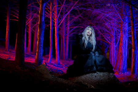 Portrait of a girl in the dark forest with colorful lights around her