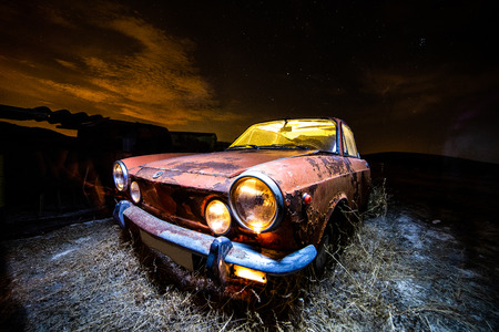 Ancient car abandoned in the countryside and illuminated with lanterns 写真素材 - 109412156
