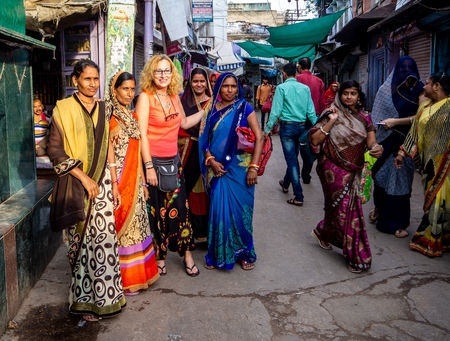Jaipur, India, 18th to 22nd September 2018 A group of Indian women pose for a photograph next to a European woman at a food market.