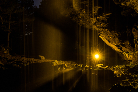 Night photograph inside a cave with waterfall and illuminated with coloured lanterns to highlight the figure of the model.