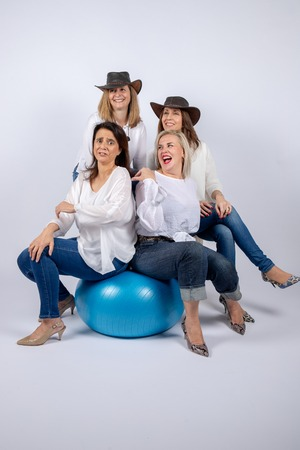 Group of 4 women, friends, middle-aged having fun in a photo session in a studio with white background, sitting on a ball