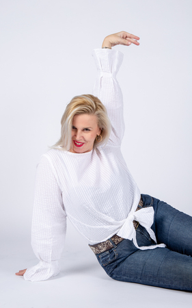 Photographic studio session for a 50 year old woman sitting on the floor and dressed in jeans and white shirt.