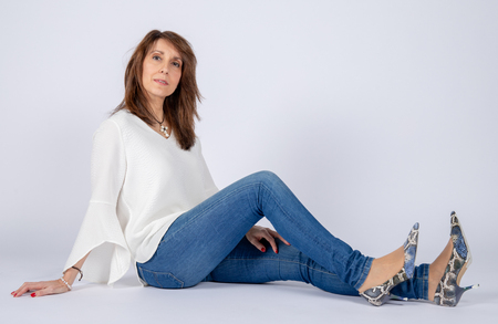Photographic studio session for a 50 year old woman sitting on the floor and dressed in jeans and white shirt. Stock Photo - 118141286