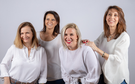 Group of 4 women, friends, middle-aged having fun in a photo session in a studio with white background