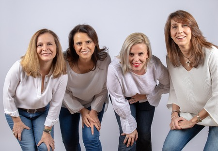 Group of 4 women, friends, middle-aged having fun in a photo session in a studio with white background Stock Photo