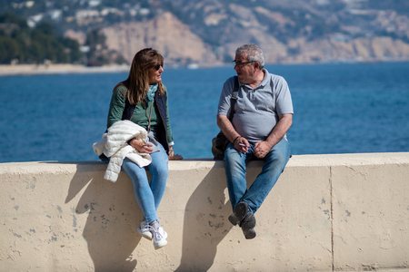 Mature Couple Talks Relaxed by the Sea