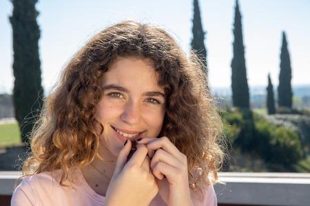 Retrato de una niña preadolescente posando en un parque público en un día soleado de primavera Foto de archivo