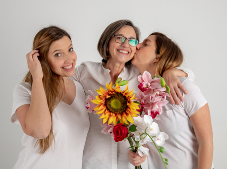 Studio portrait session with mother and two twin sisters who enjoy a very funny attitude with a big sunflower in their hands. Stok Fotoğraf