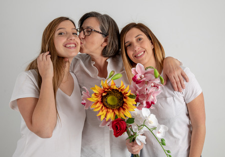 Studio portrait session with mother and two twin sisters who enjoy a very funny attitude with a big sunflower in their hands. Standard-Bild