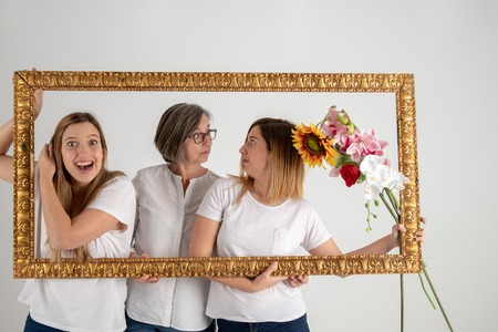 Family composed by mother and two twin sisters pose inside a pictorial frame in a photographic studio and in a very funny attitude.