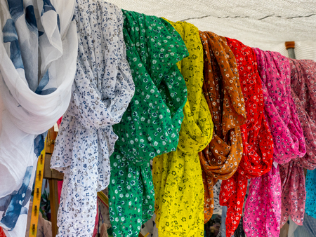 Image of some foulards in different colors hanging in a flea market