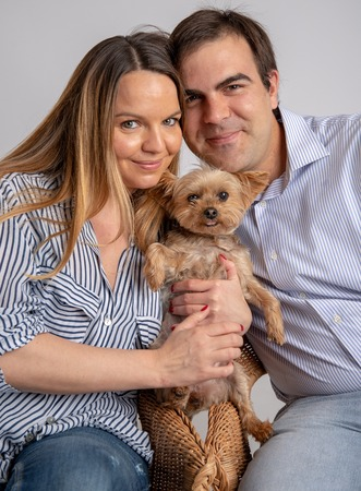 Young couple pose in a photography studio sitting in a chair with a yorkshire dog. Stock Photo