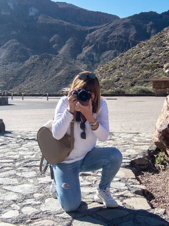 Mature woman takes pictures of kneeling to a landscape in Los Roques, next to the Teide in Tenerife, Canary Islands, Spain Stock Photo