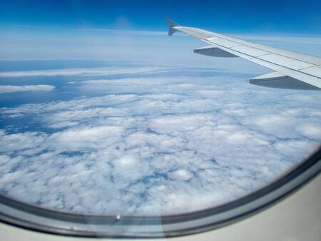 Cloud landscape seen from the inside, through the window of a commercial airplane Foto de archivo