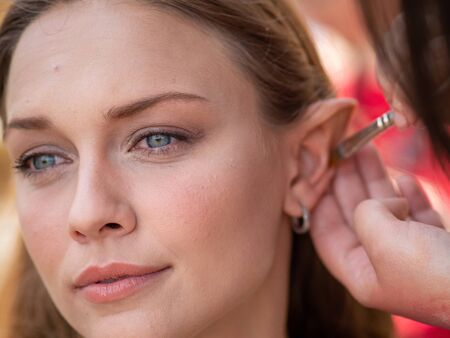 Makeup on the ears to a model to turn her into an elf Imagens