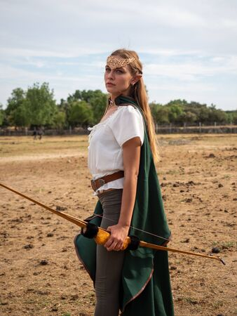 Blonde girl with blue eyes and makeup with elf ears poses in the field with a bow and a green cape.