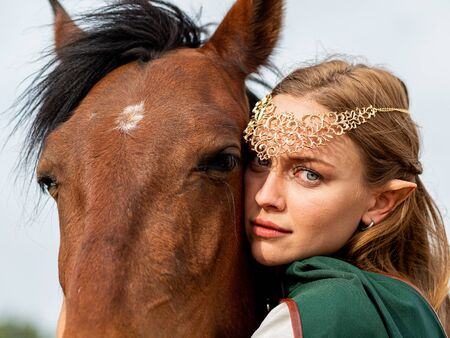 Blonde girl with blue eyes and makeup with elf ears and a tiara on her head poses in the field with a brown horse and a green cape. Stock Photo