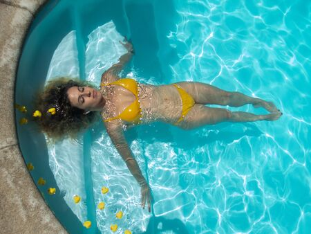 Girl in yellow bikini floats in the pool with rubber ducklings Stok Fotoğraf