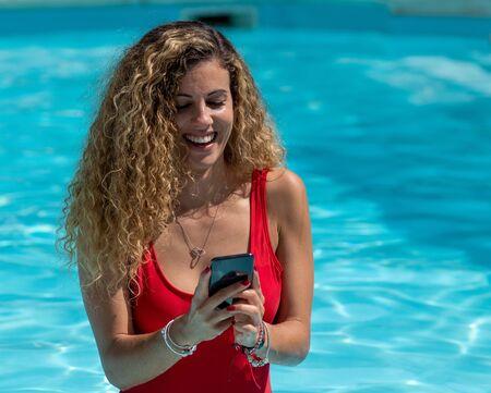 Chica rubia usa teléfono móvil dentro de la piscina