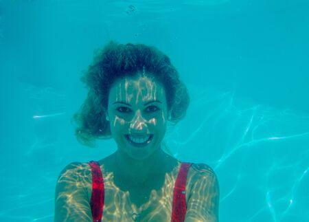 Underwater photograph of blonde girl with curls and red swimsuit