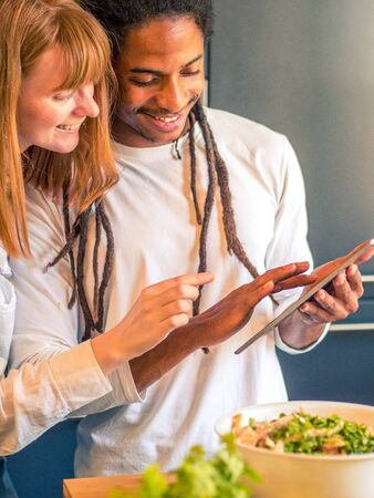 Interracial couple formed by African and Caucasian prepare a salad together with the help of their cell phone Banco de Imagens