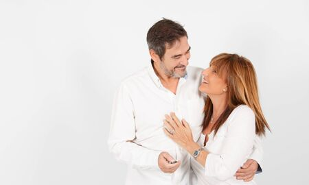 A 50-year-old adult couple poses in a photographic studio in a cheerful way with a white