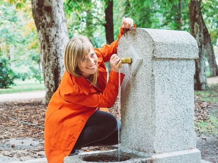 Caucasian girl with red gabardine drinks water from a fountain in a park in Madrid 写真素材