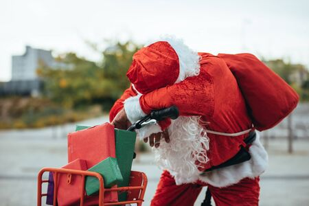 Vertical stock photo of santa claus supported in a bicycle full of gifts with exhausted expression. Christmas time Reklamní fotografie