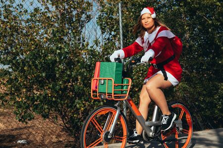 Stock photo of Mama noel riding a bicycle with some gifts in it along the street . Christmas time 写真素材
