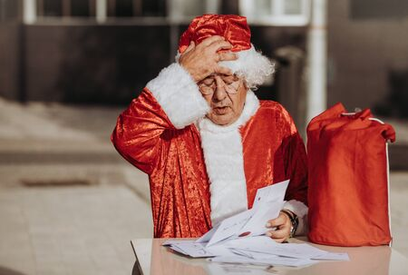 Stock photo of Santa claus without beard sitting on a terrace organizing Christmas cards with a red bag on the table. Christmas time Zdjęcie Seryjne