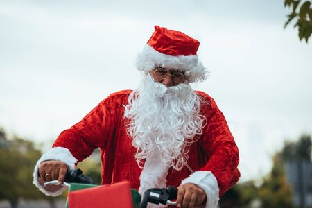 Stock photo of Santa Claus with gifts in the bicycle and his red suitcase on his back. Christmas time Stock Photo