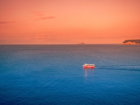 Stock photo of sunset on the sea with a small boat sailing Stock fotó