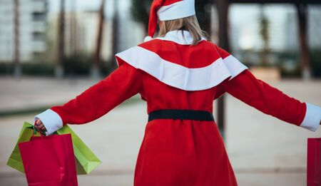 stock photo of mama noel with skates holding a lantern with gift bags in hand. Christmas time