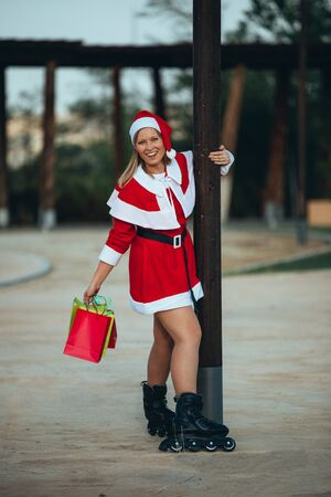 Vertical stock photo of mama noel with skates holding a lantern with gift bags in hand. Christmas time Reklamní fotografie