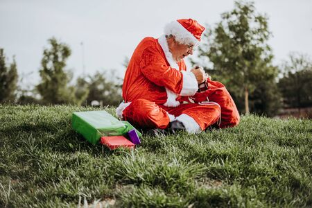 Vertical stock photo of Santa Claus without beard crouched on the floor organizing gifts with his red bag. Christmas time