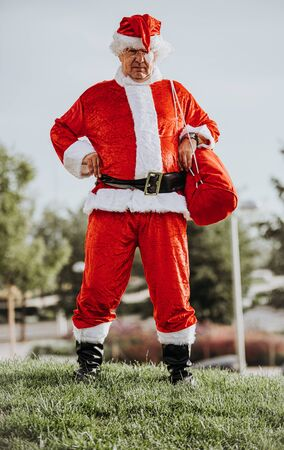 Stock photo of Vertical photo of papa noel without beard with arms resting on the body and yawning. Christmas time