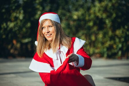 Stock photo of Mama Noel walking down a street with trees with the bag of gifts in hand. Christmas time