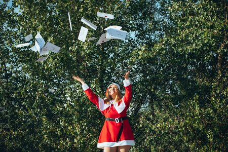 Stock photo of Mama noel throwing Christmas cards in the air in the middle of the street. Christmas time Reklamní fotografie