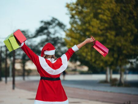 Stock photo of mama noel with skates holding a lantern with gift bags in hand. Christmas time Reklamní fotografie