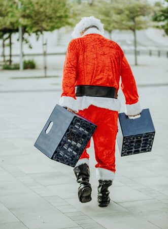 Vertical stock photo of papa noel without beard loading with two boxes of beer. Christmas time