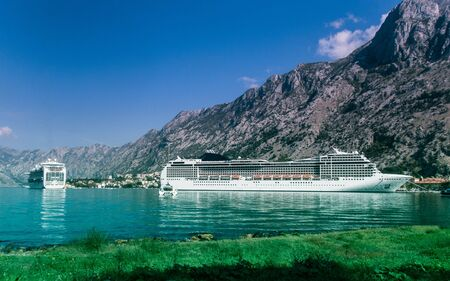 Stock photo of a cruise moored in port with the mountains in the background in Kotor, Montenegro