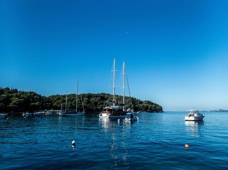 Stock photo of sailboats moored in the calm sea in Cavtat, Croatia. Travel concept