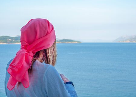 Stock photo of Woman with a pink scarf on her back looking at the sea from the balcony. Cancer